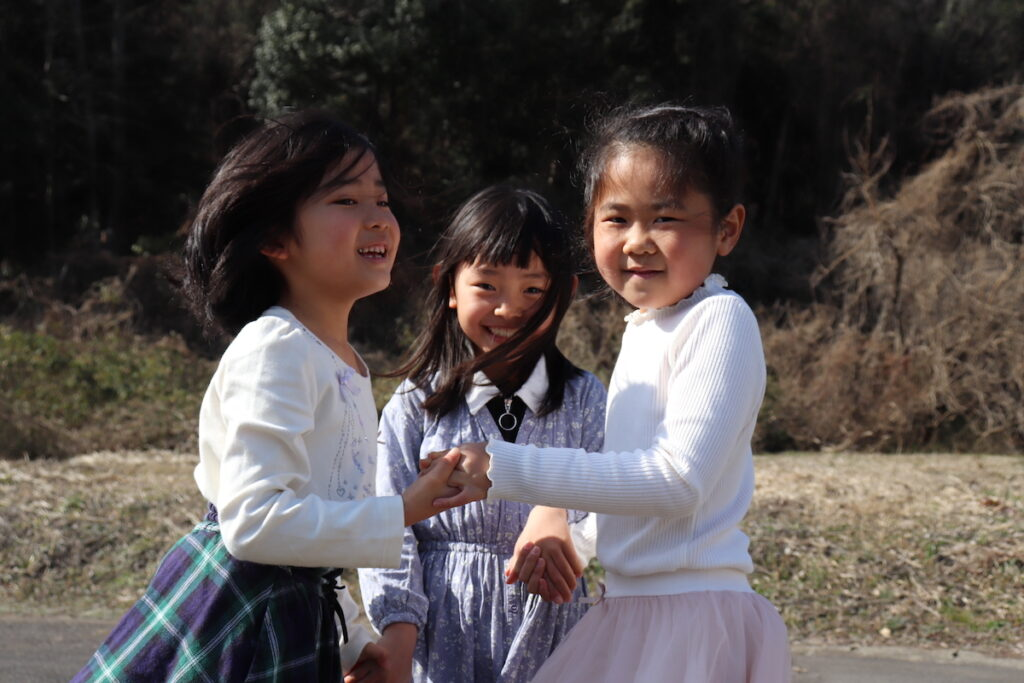手を繋いで楽しく遊ぶ子供たちの写真